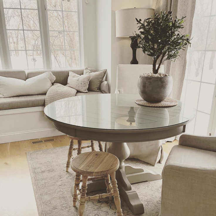 Serene and neutral European country inspired breakfast nook with window seat, round dining table, and Belgian slope arm chairs - Hello Lovely Studio.