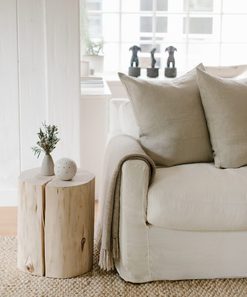 Jenni Kayne cedar stump with linen sofa in a lovely tranquil natural luxe space.