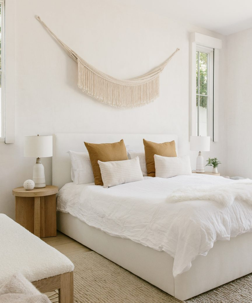 Natural, quiet, subdued mood in a lovely Jenni Kayne bedroom with macrame wall hanging.