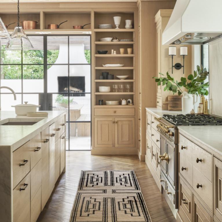 Modern rustic warmth in a kitchen with tone on tone light neutrals, herringbone wood floors, and luxurious range - Lulu & Georgia.