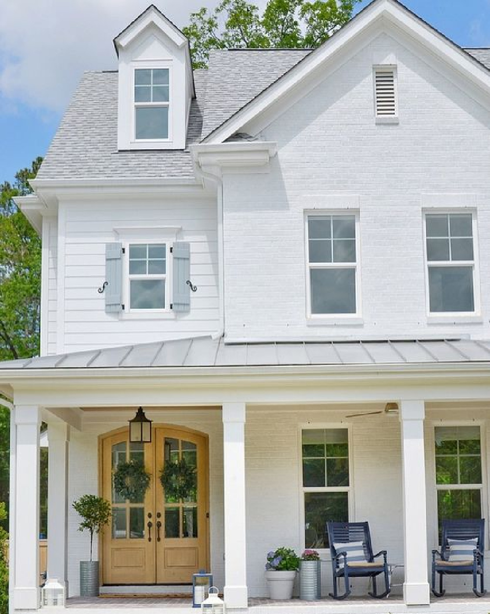 Sherwin Williams Extra White paint color on a gorgeous modern farmhouse with blue shutters - CrissyMarieBlog. #whitehouses #swextrawhite #whitepaintcolors
