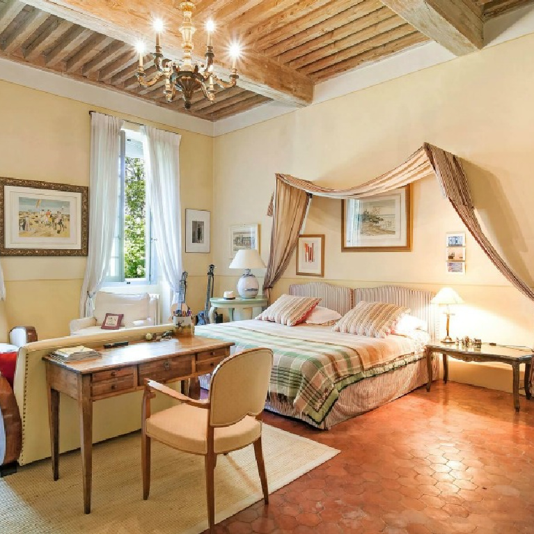 Elegant French country bedroom with sitting area in a Provence chateau with wood ceilings, yellow walls, and Old World built-ins - Haven In.