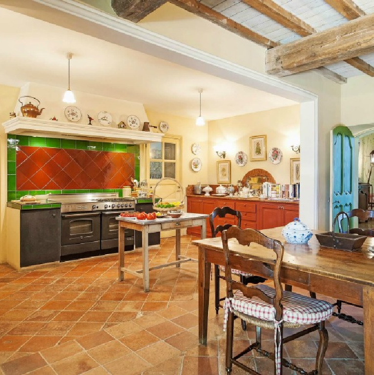 Cheerful and traditional with terracotta, green, and bright blue accents, this Provence kitchen with work table boasts timeless charm - Haven In. #frenchcountry #kitchens