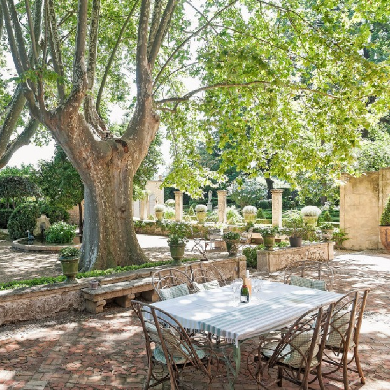French formal gardens and tree shaded outdoor dining with pea gravel - see more of this Stunning French Château Near St-Rémy-de-Provence by Haven In. #frenchgarden #frenchcountry #frenchchateau