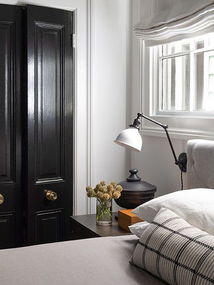 Understated and classic bedroom with glossy black closet doors in a room with design by Brian Paquette.