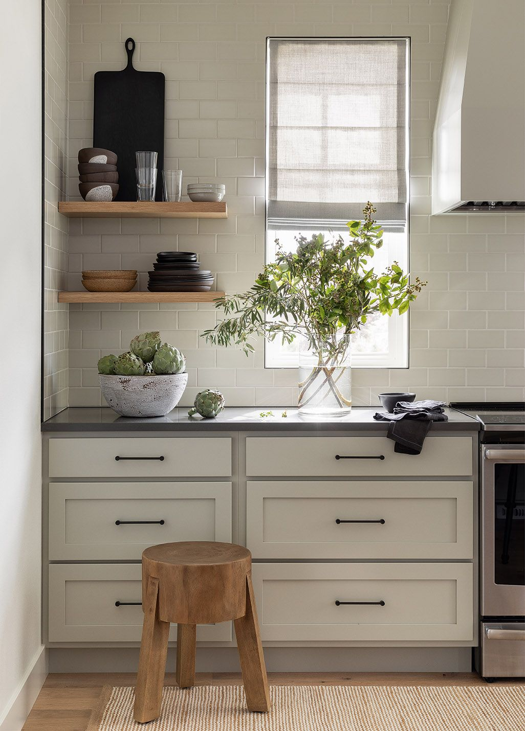 Rustic wood stool and floating shelves in a beautiful kitchen with design by Brian Paquette. #kitchendesign #floatingshelves