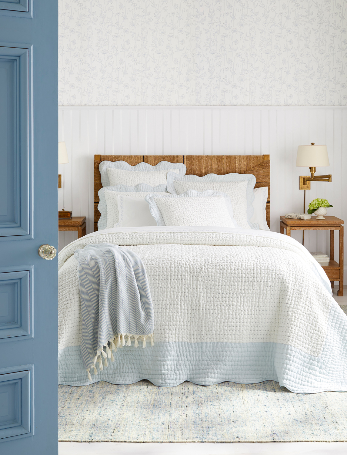 Coastal bedroom with classic blue painted vintage door and soft, airy, light and bright white quilt with light blue band - Serena & Lily.