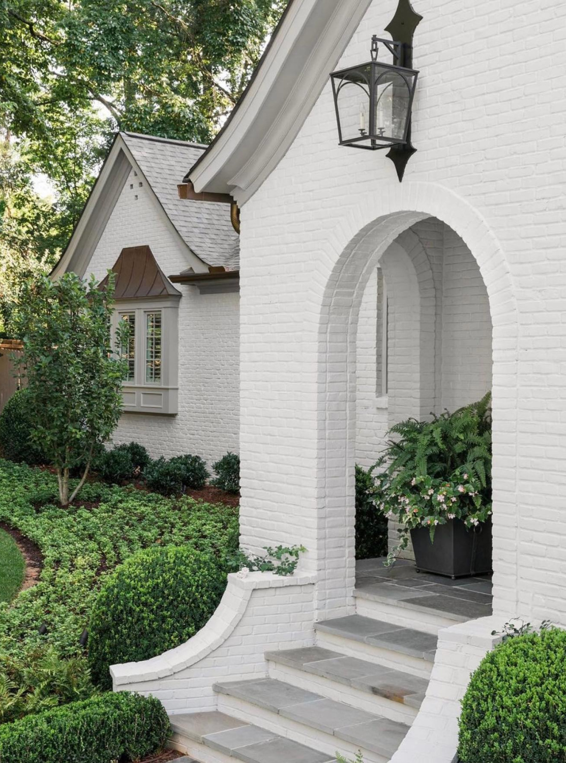 Balboa Mist (Benjamin Moore) on brick exterior of a lovely home with arches (Ladisic Fine Homes) - Sherry Hart. #balboamist #benjaminmoorebalboamist #paintcolors #housecolors