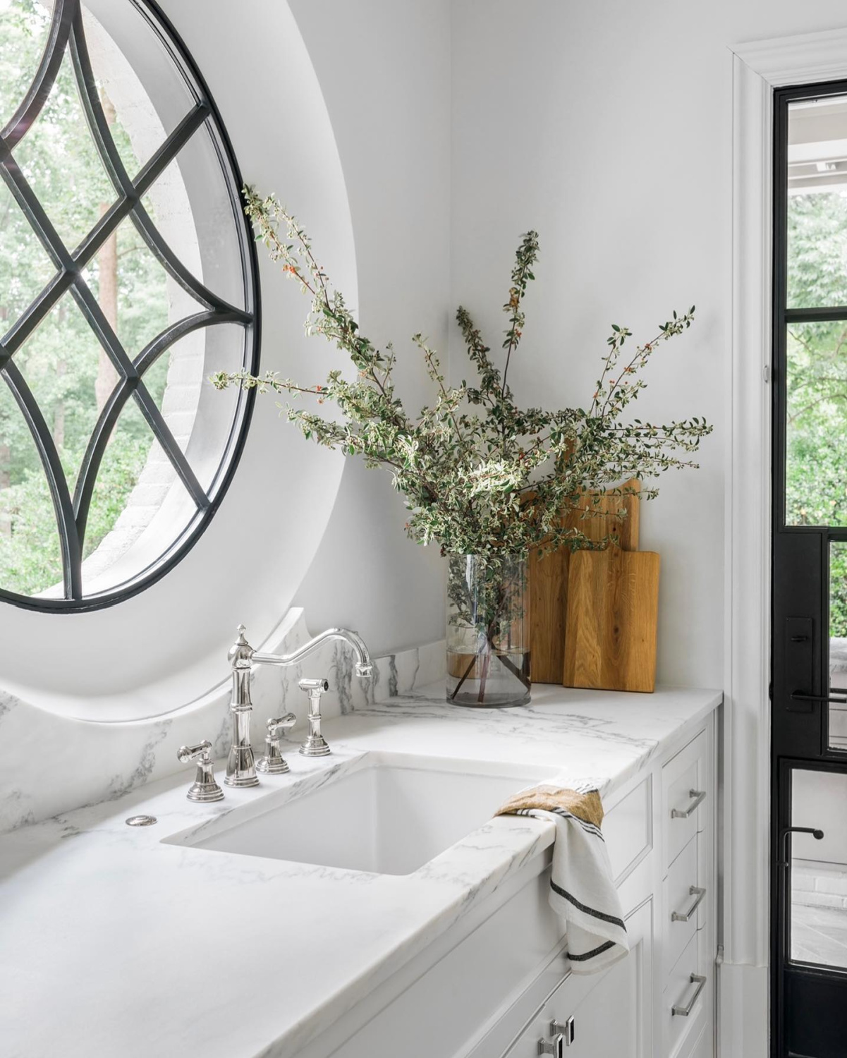 A gloriously elegant white kitchen with iron door and decorative window - Ladisic Fine Homes and Sherry Hart. #whitekitchens #elegantkitchens #irondoor #decorativewindow
