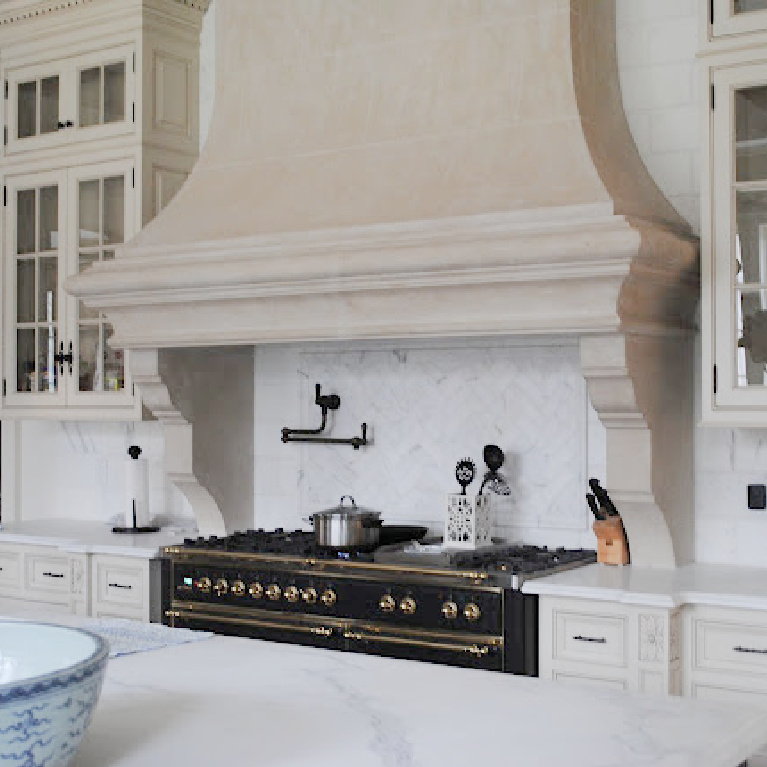 Image result for enchanted home Tina's kitchen with detail of stone range hood and glass front cabinets