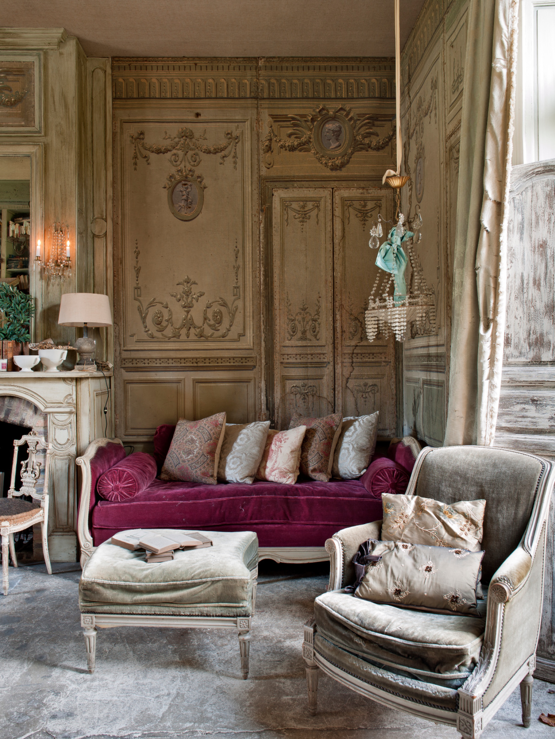 A traditional sitting room with painted walls and, unusually, a concrete floor. A sofa with a maroon red cushion stands in one corner. Featured in Shauna Varvel's PROVENCE STYLE. #interiordesign #frenchcountry #oldworldstyle #velvet