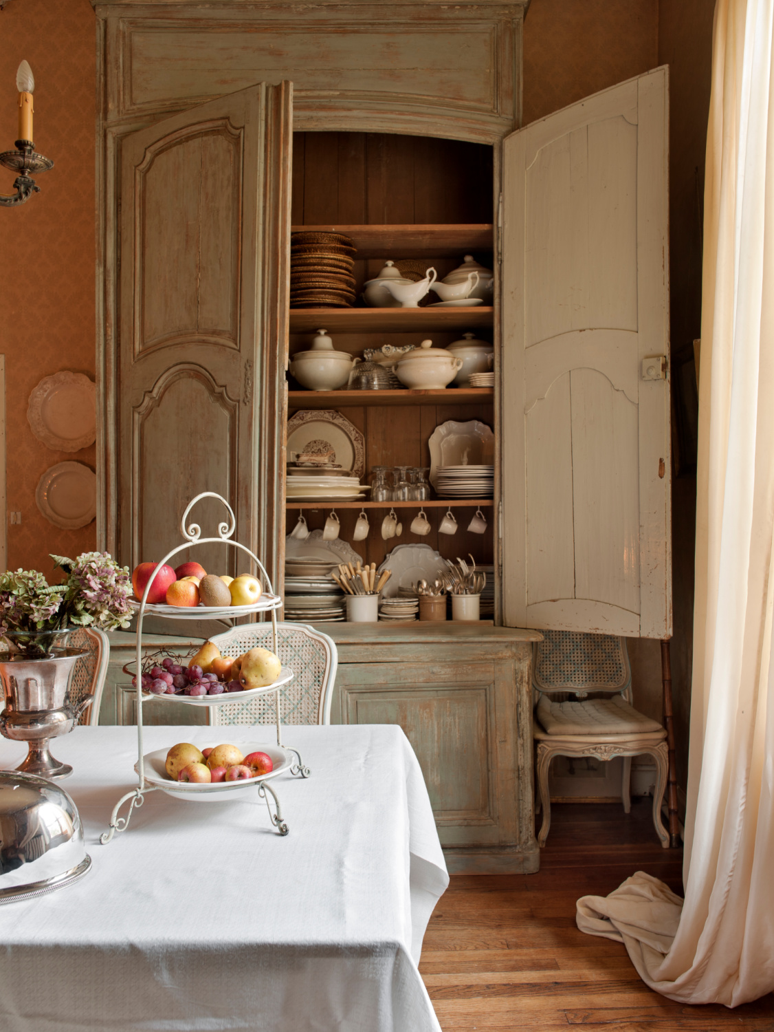 Distressed pale French grey dining room cupboard is full of traditional style china treasures. Featured in Shauna Varvel's PROVENCE STYLE. #interiordesign #frenchcountry #oldworldstyle