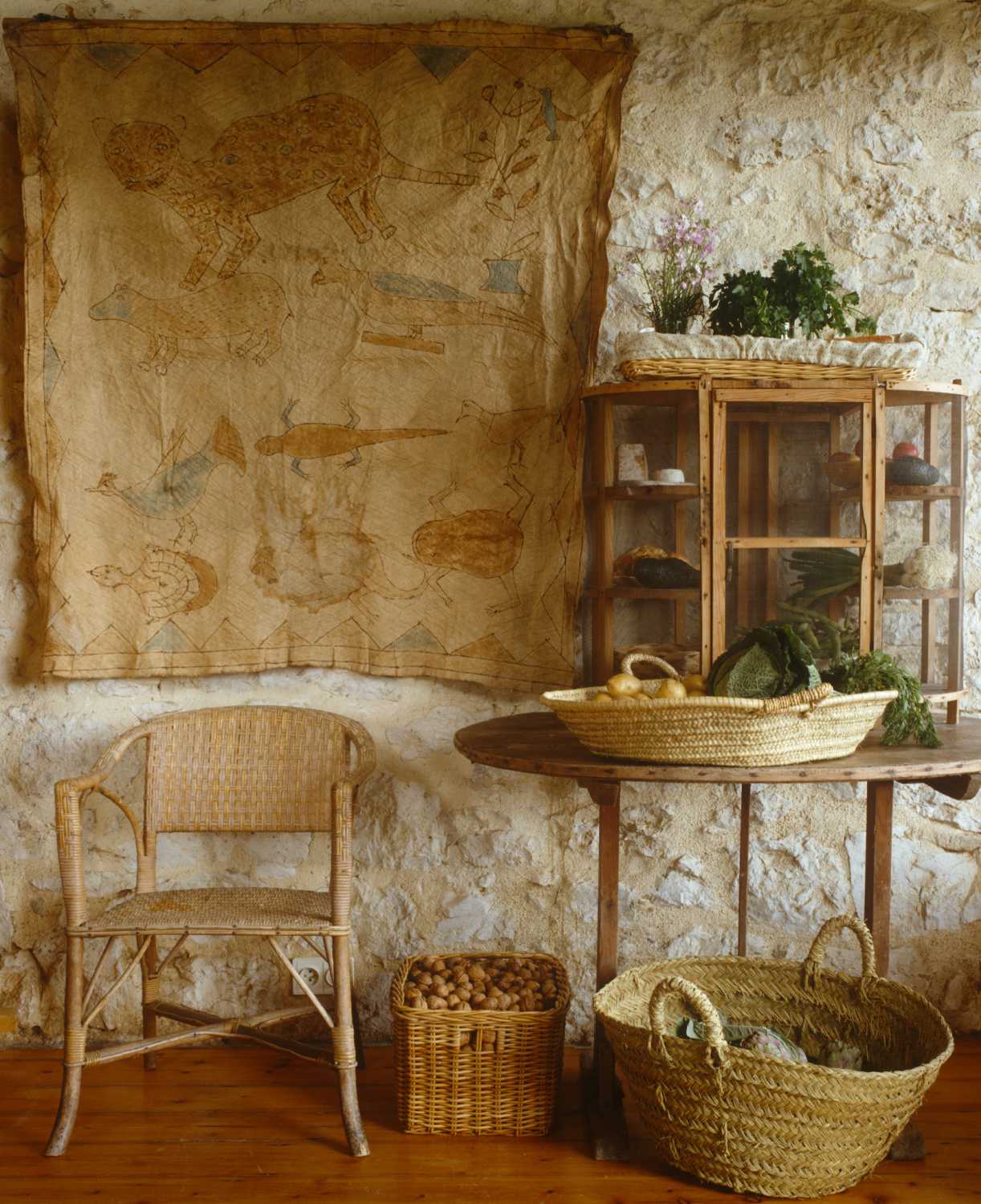 A primitive bark painting from Bali hangs beside an English larder sitting on a 'vigneronne', a collapsible table used by the grape pickers for lunch during the harvest. Featured in Shauna Varvel's PROVENCE STYLE. #interiordesign #frenchcountry #oldworldstyle