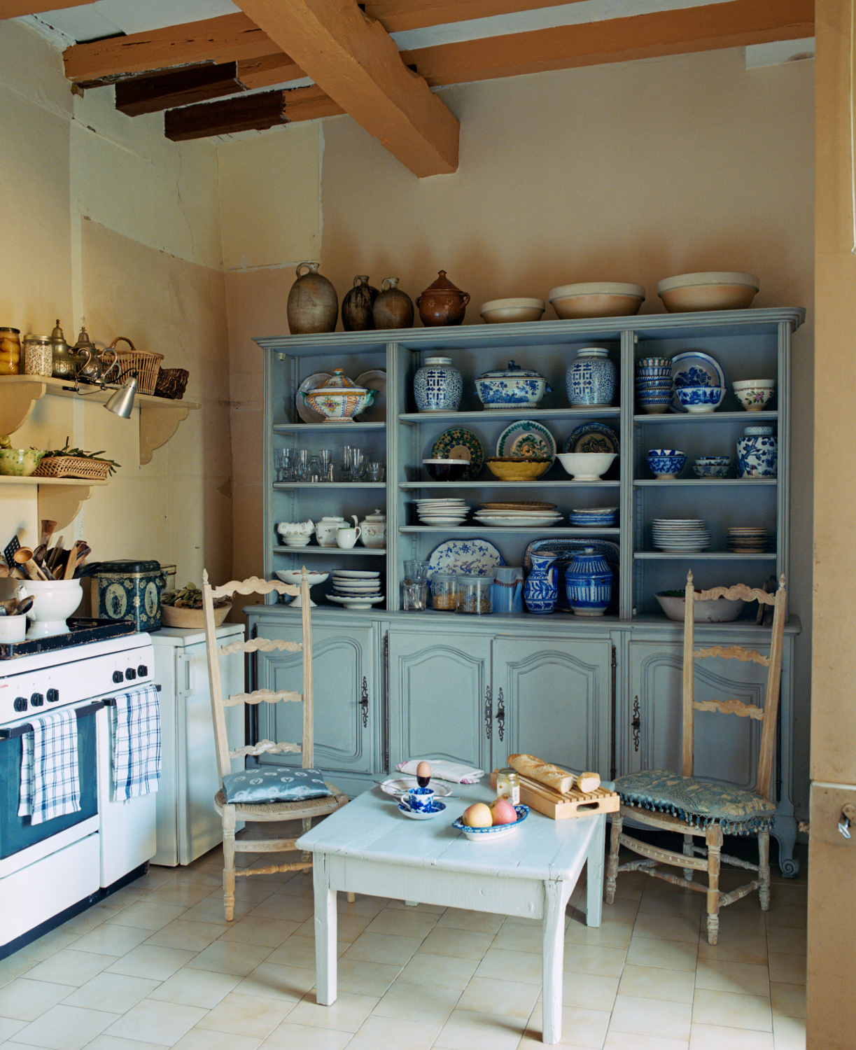 A pair of high-backed kitchen chairs in front of the  large blue dresser in the kitchen displaying a collection of ceramics from North Africa, Andalucia, China and Holland. Featured in Shauna Varvel's PROVENCE STYLE. #interiordesign #frenchcountry #oldworldstyle