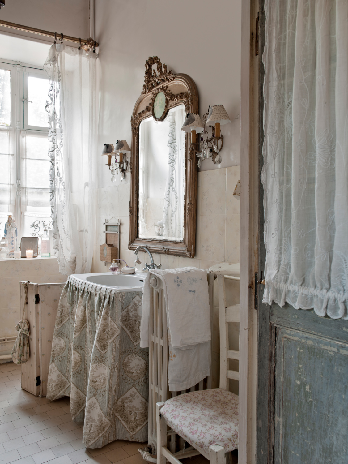 Elegant and traditional bathroom in Provence with ornate mirror, skirted sink, and a pale palette. Featured in Shauna Varvel's PROVENCE STYLE. #interiordesign #frenchcountry #oldworldstyle