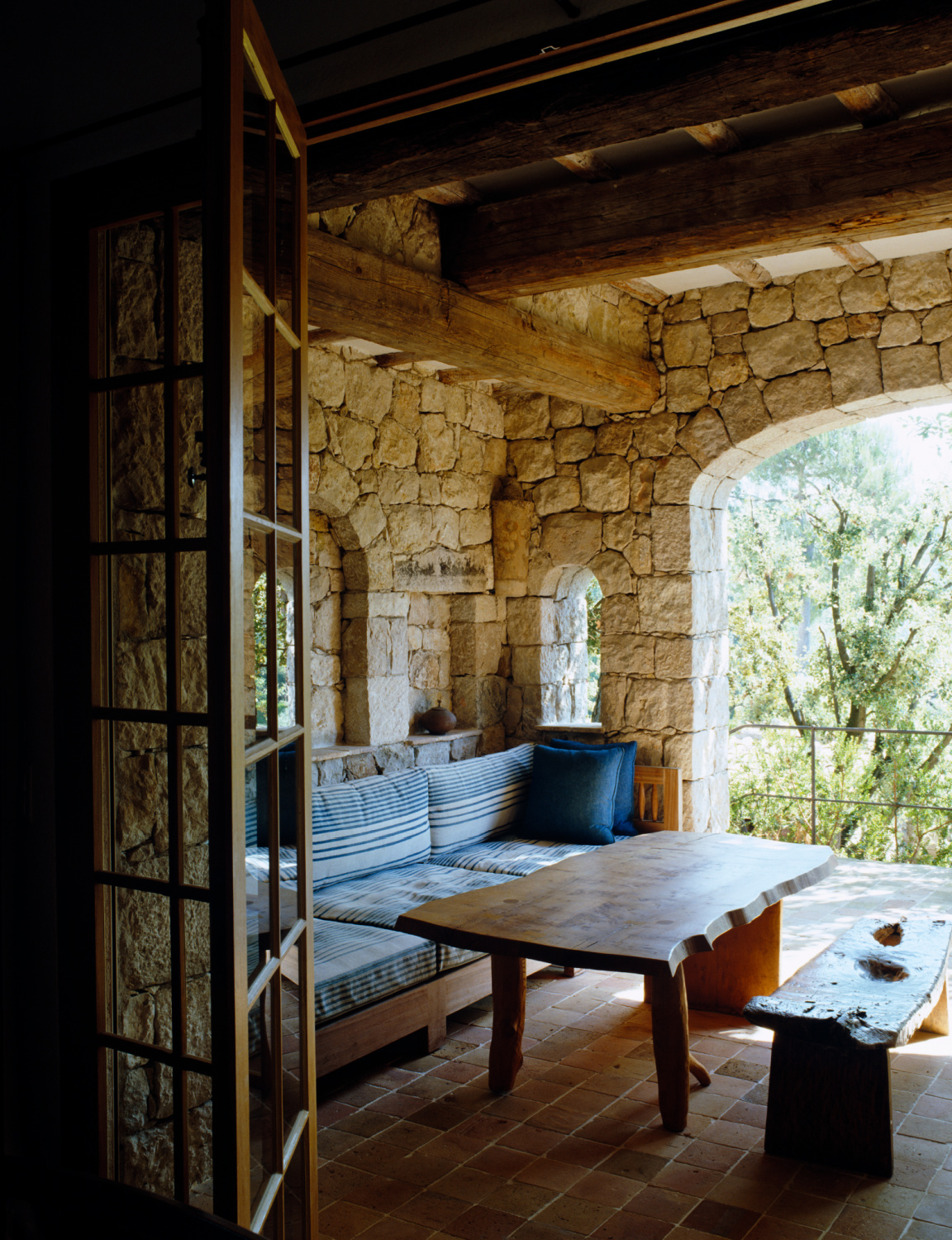 Rugged stone walls and patina-ed beams and arch details comprise a Provence outdoor living area with rustic furnishings. Featured in Shauna Varvel's PROVENCE STYLE. #interiordesign #frenchcountry #oldworldstyle