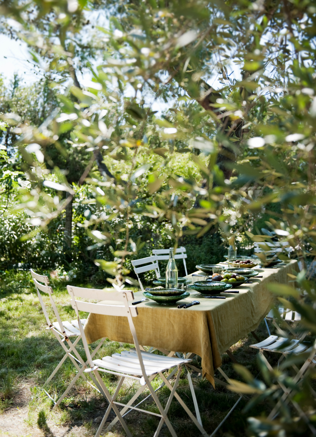 trees a table is laid for lunch in the garden. Featured in Shauna Varvel's PROVENCE STYLE. #interiordesign #frenchcountry #oldworldstyle