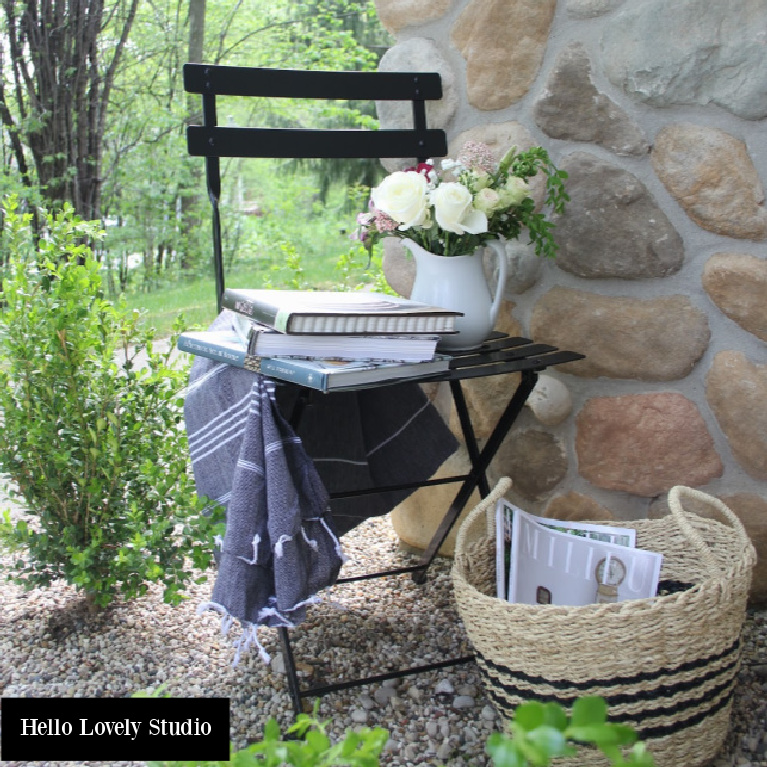 Black Fermob bistro chair, stripe Turkish towel, and seagrass basket for a charming outdoor French farmhouse vignette - Hello Lovely Studio.
