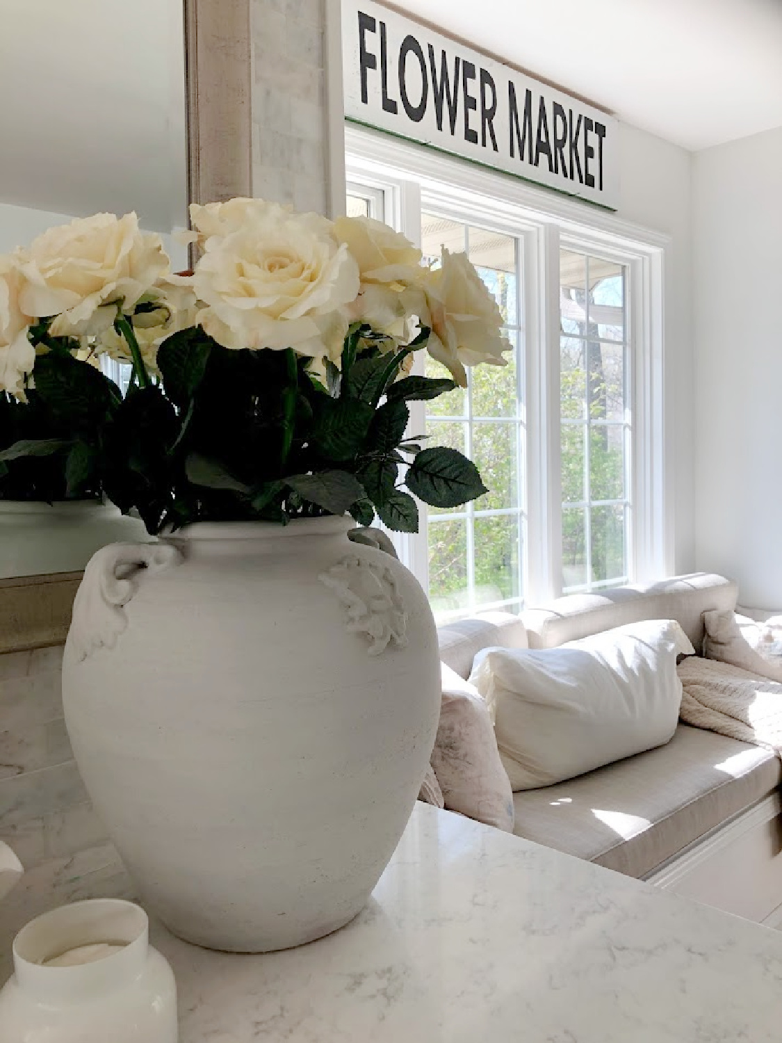 White roses in an antique white urn on my counter in the kitchen with window seat - Hello Lovely. #serenedecor #whiteroses #modernFrench