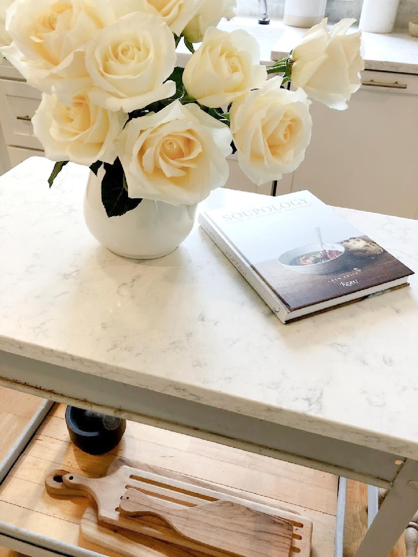 White roses in vintage ironstone pitcher on an industrial steel cart in my serene white kitchen - Hello Lovely. #whitekitchens #modernfrench #farmhousekitchen