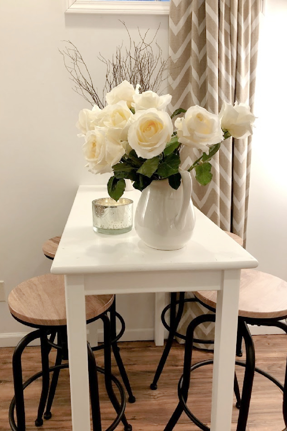 White roses in ironstone pitcher on pub table with industrial stools - Hello Lovely.