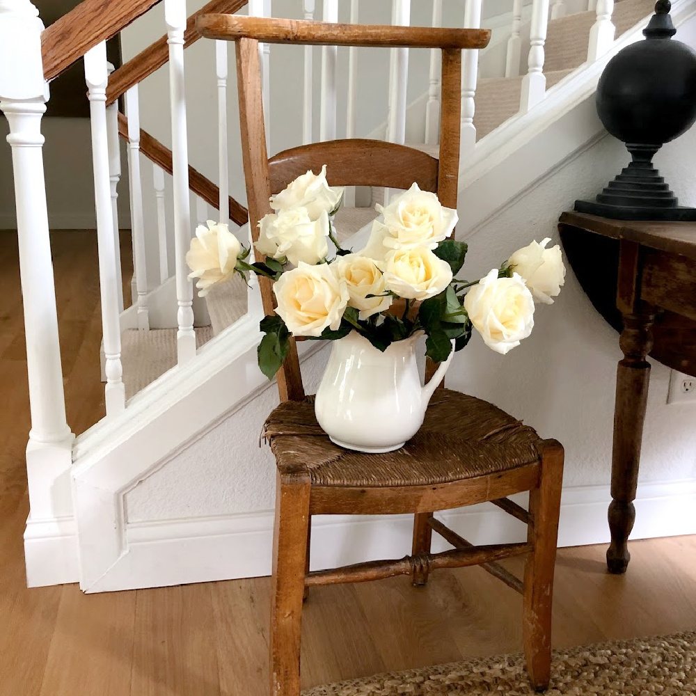 White roses in ironstone pitcher on French prayer chair - Hello Lovely.