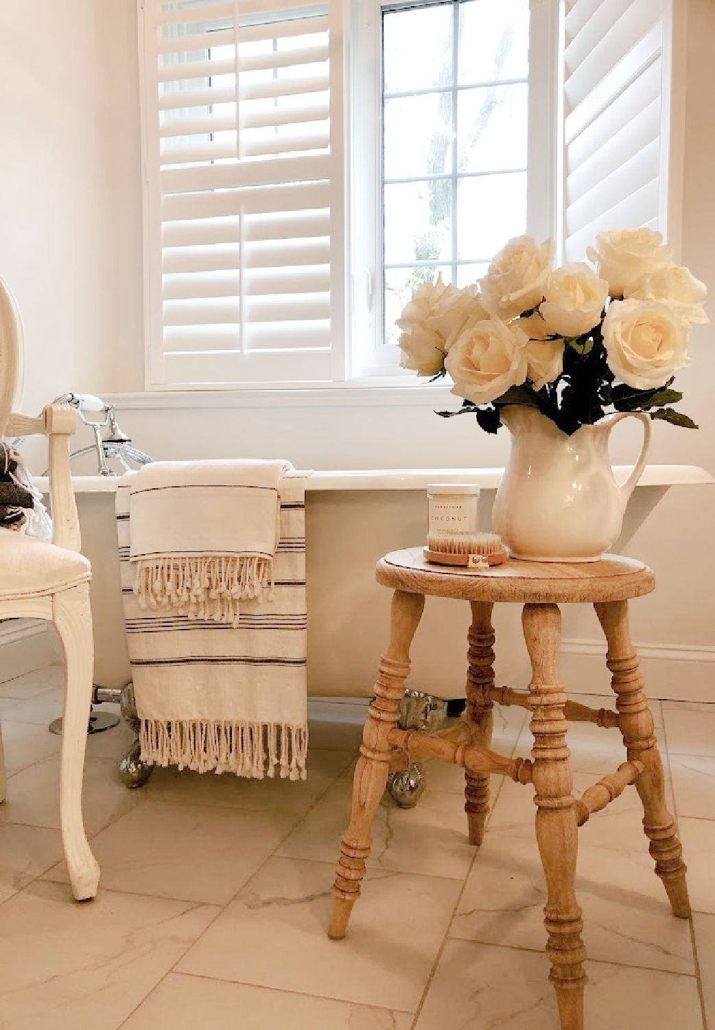 French country white bathroom with maids tub, accent stool, and white roses - Hello Lovely.