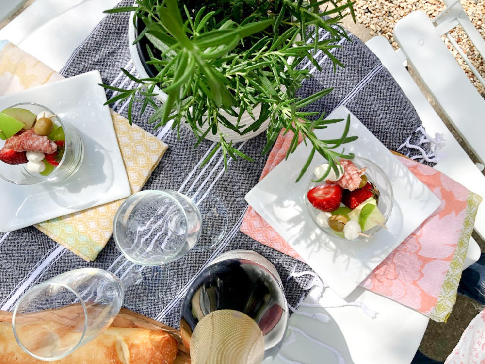 Baguettes, champagne, and simple jarcuterie (cheeseboard in a jar!) for a charming French picnic outside - Hello Lovely Studio.
