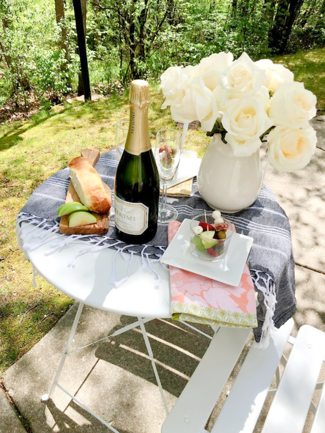 Petite French bistro table set with champagne, jarcuterie, and white roses - Hello Lovely Studio. #outdoordining #entertaining #frenchpicnic #jarcuterie