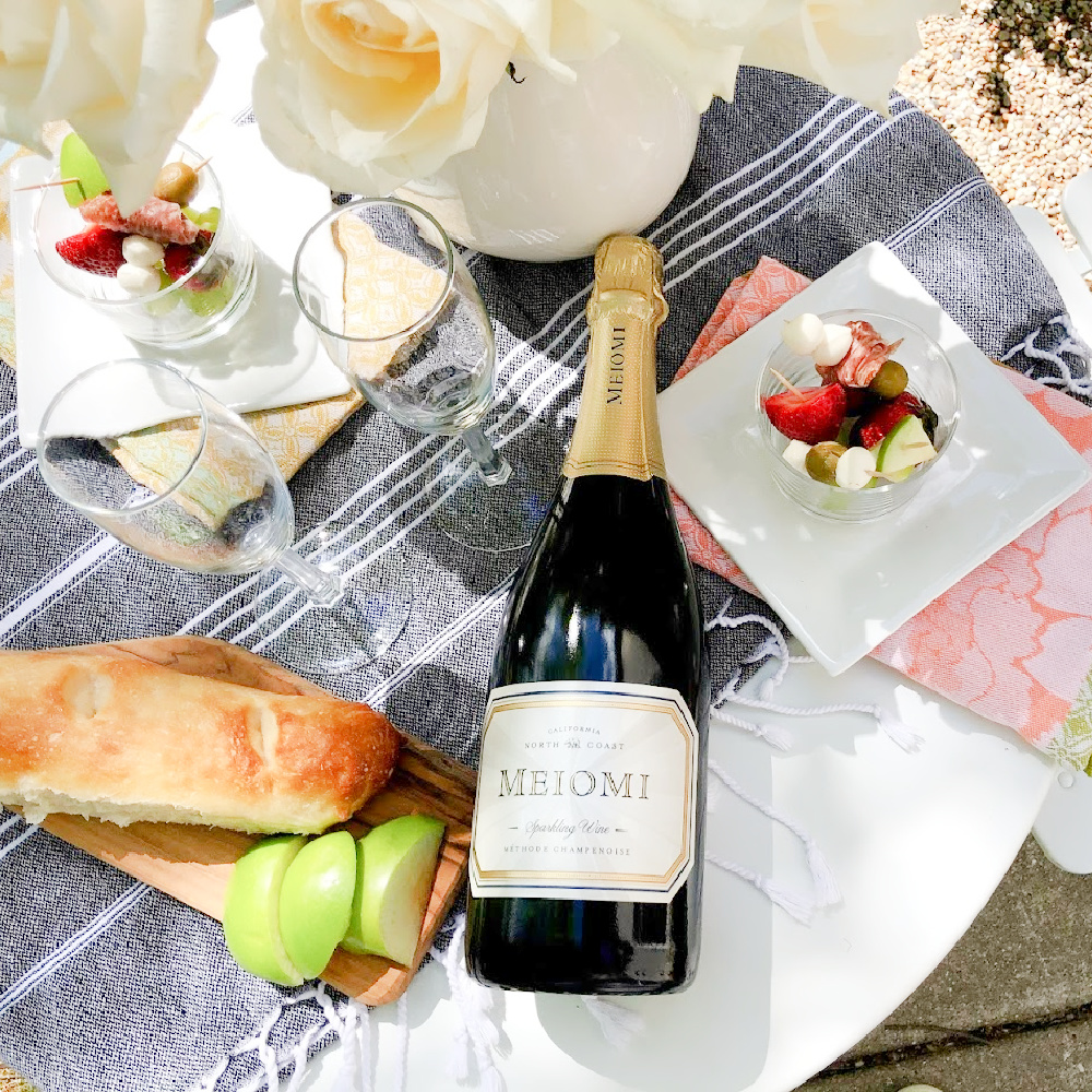 Champagne, jarcuterie and baguette on a charming French cafe dining table in garden - Hello Lovely Studio. #jarcuterie #frenchpicnic #frenchaesthetic #outdoordining