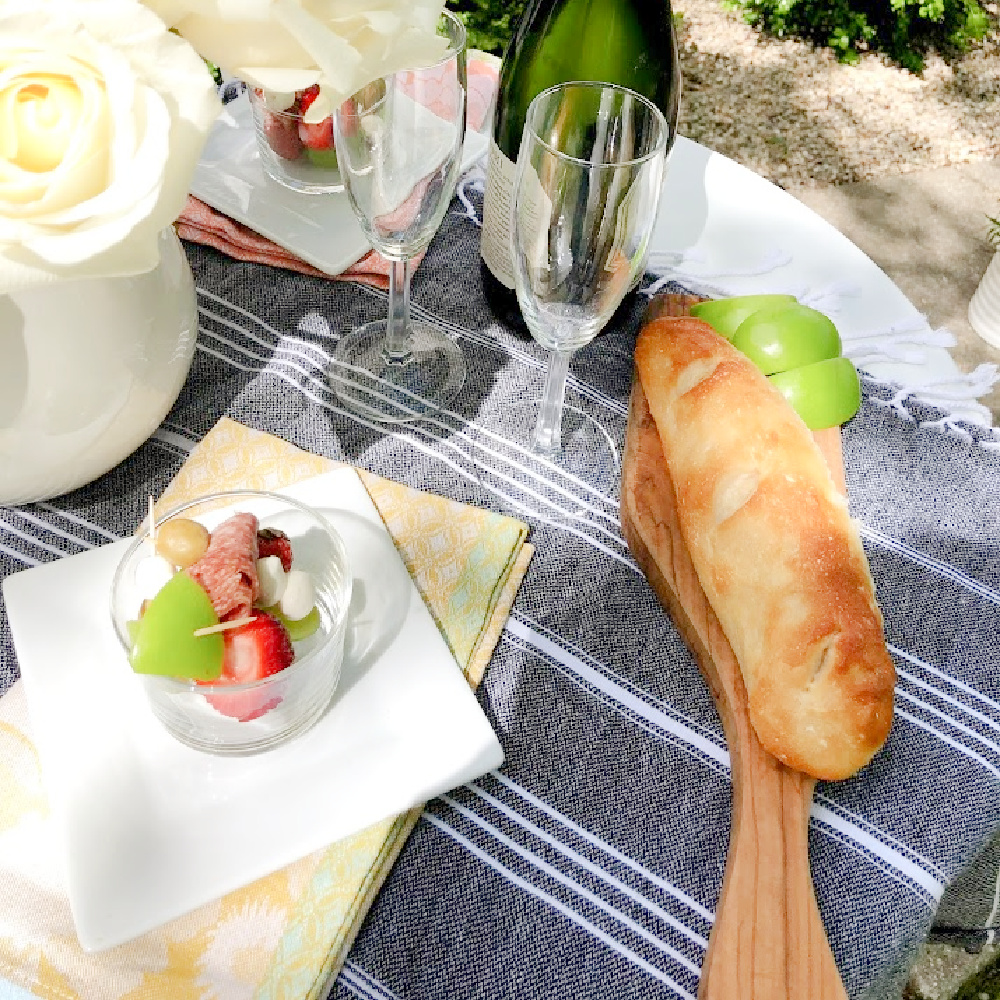 Jarcuterie and baguette on a charming round French cafe dining table in the garden - Hello Lovely Studio. #jarcuterie #frenchpicnic #frenchaesthetic #outdoordining