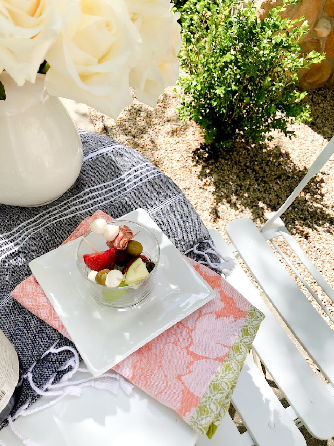 Jarcuterie is served on a charming French cafe dining table in the garden - Hello Lovely Studio. #jarcuterie #frenchpicnic #frenchaesthetic #outdoordining