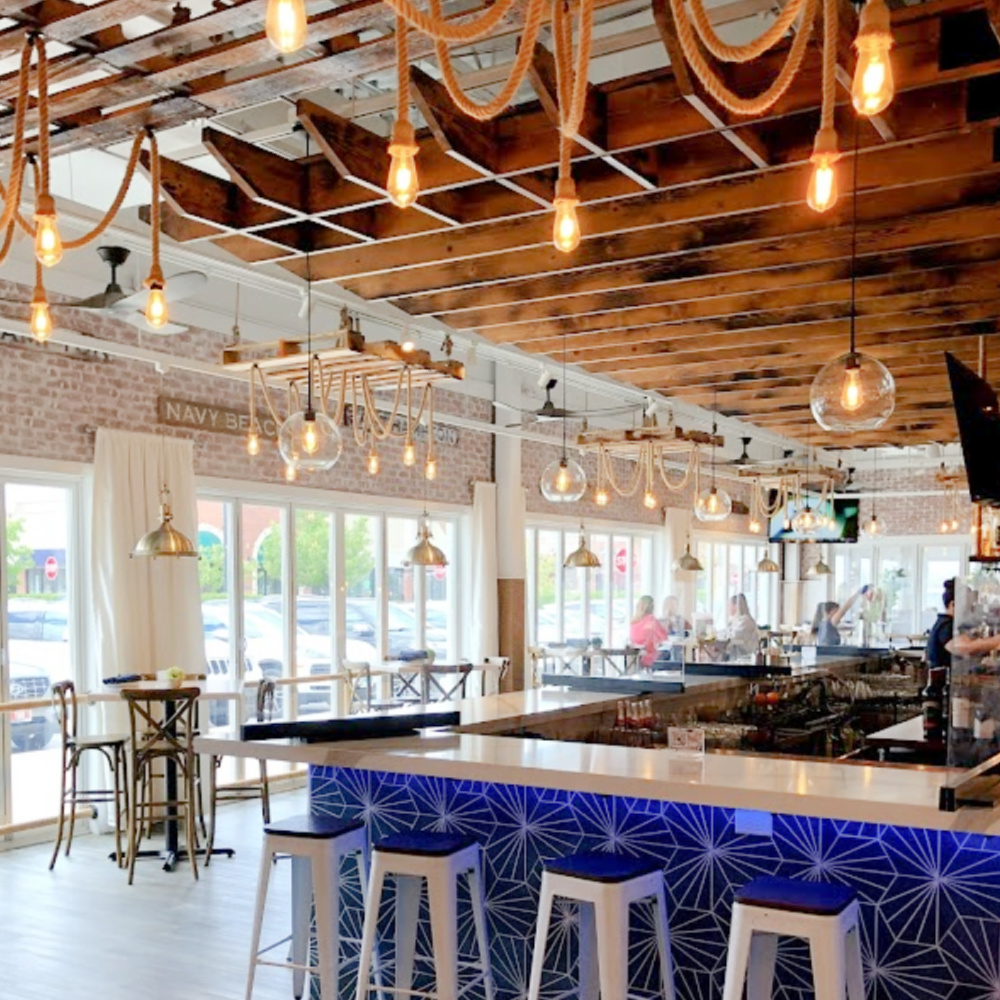 Nautical rope pendant lights illuminate the ceiilng and impart coastal vibes at The Hampton Social in South Barrington - Hello Lovely Studio. #coastaldesign #thehamptonsocial #hamptonstyle