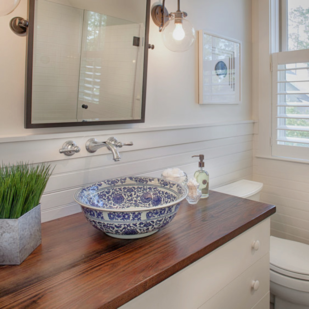 Blue and white vessel sink basin on a wood topped vanity in a coastal beathroom with wainscot and wall mount faucet. Design by Lisa Furey. #coastalstyle #bathroomdesign #vesselsink #blueandwhite #traditionalstyle