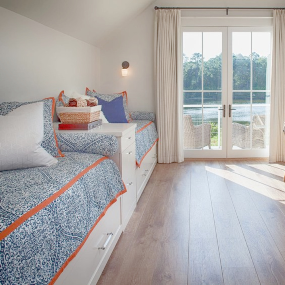 Blue bunk room in carriage house with built in beds, blue and white decor, bistro chairs, and wide plank wood flooring. Design by Lisa Furey. #bunkroom #captainsbeds #blueandwhite #bedroomdesign #coastalstyle