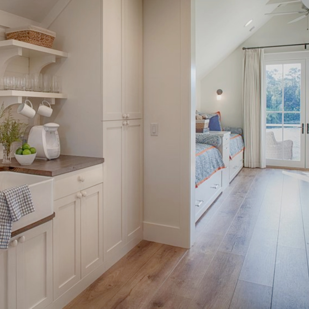 Kitchen with farm sink, wide plank wood flooring, built in captains beds and French doors to deck in carriage house with coastal and Shaker style. Design by Lisa Furey. #coastalstyle #modernfarmhouse #carriagehouse #interiordesign