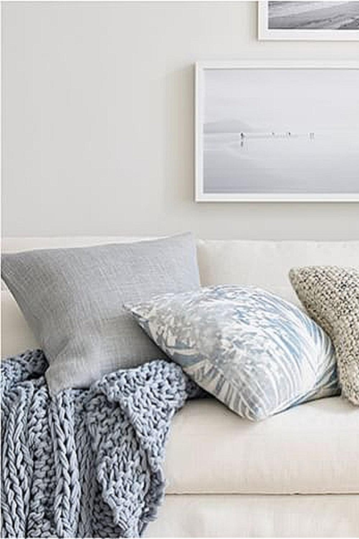 Beachy linen sofa with Pottery Barn blue gray linen pillows and chunky knit throw.