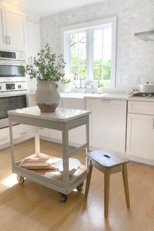 Hello Lovely Studio's serene white kitchen with an industrial cart repurposed as a work table. #whitekitchens #europeancountry #coastalkitchen #industrialcart