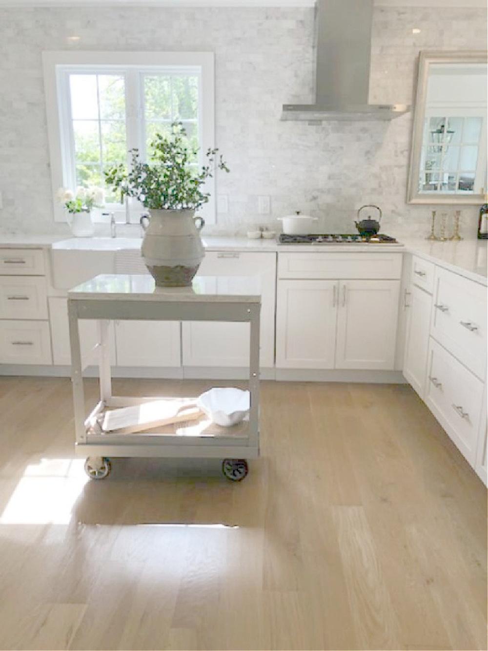White oak hardwood floors in a serene simple Shaker modern farmhouse kitchen by Hello Lovely Studio. #hellolovelystudio #whiteoak #hardwoodfloors #kitchendesign #shakerkitchen