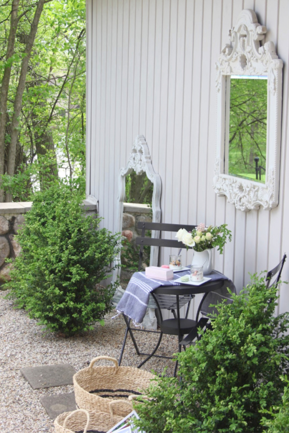 French country courtyard with boxwood, gravel, bisto set, baskets, and a French mirror. #hellolovelystudio #frenchcountry #bistroset #courtyard #gardendecor #boxwood #frenchbaskets #outdoordecor #outdooroasis