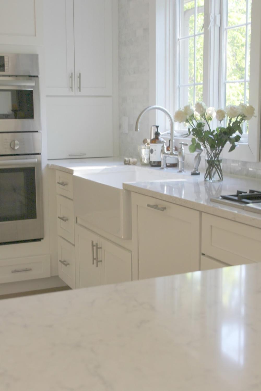 My white serene Shaker kitchen with farm sink, Bosch appliances, and Viatera (Minuet) quartz countertops - Hello Lovely Studio.