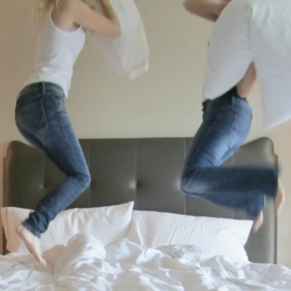 Yummy white sheets on bed and friends in denim jumping for pillow fight - Hello Lovely Studio. #whitesheets