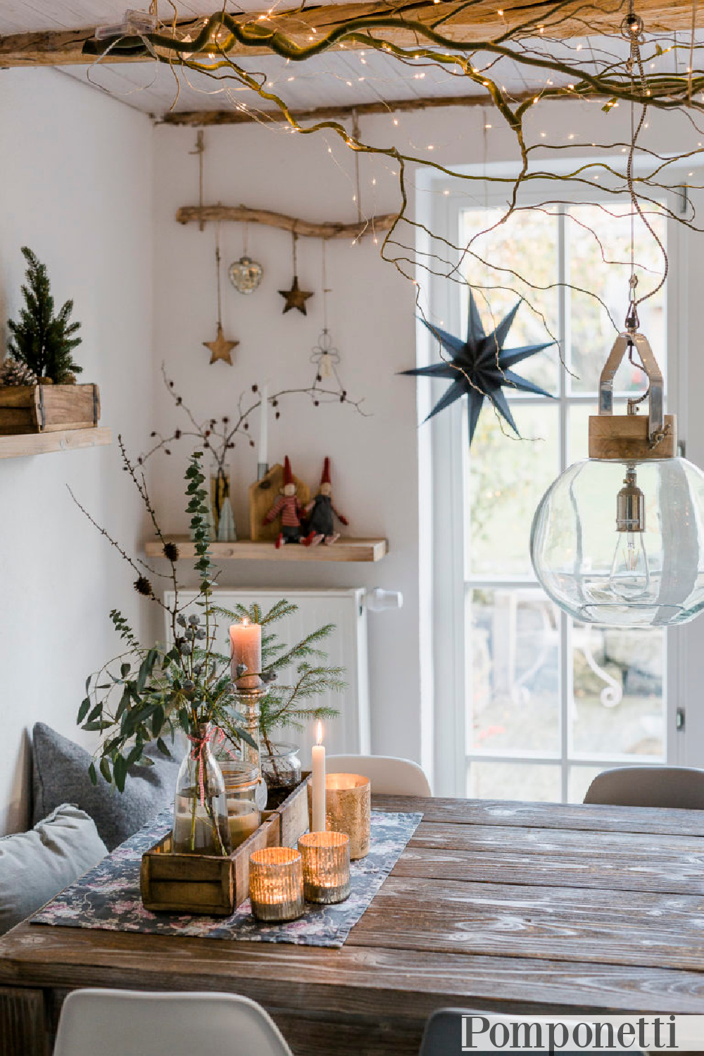 Scandi Christmas rustic decor in a dining area with driftwood, ornaments, branches, and white fairy lights - Pomponetti. #farmhousechristmas #christmasdecor #rusticchristmas #scandichristmas
