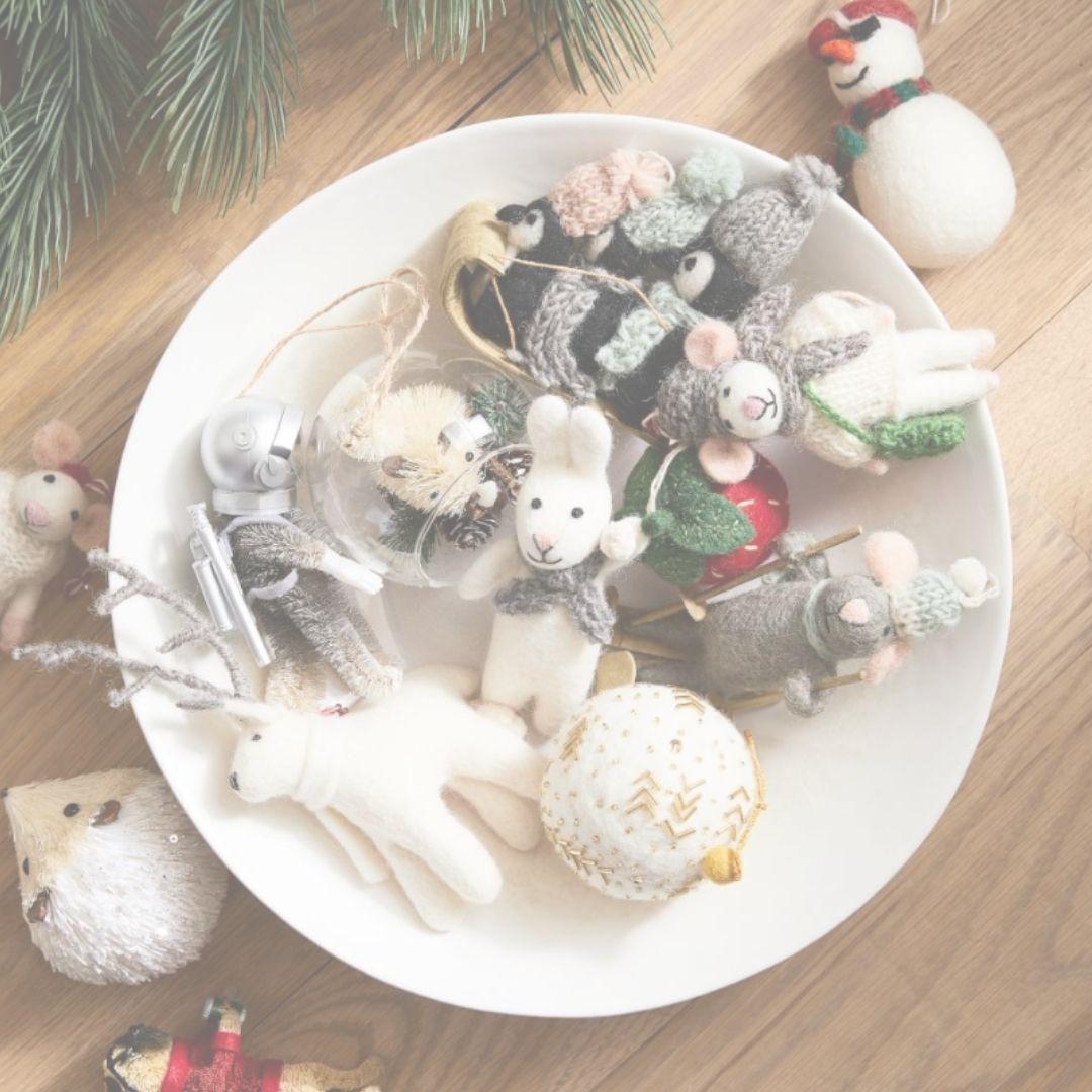 Felt Christmas tree creature ornaments massed together in bowl - West Elm. #feltornaments #christmasdecor #christmastrees