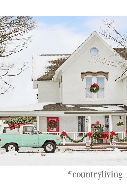 Charming white farmhouse decorated for Christmas - Country Living. #countrychristmas #farmhousechristmas #outdoorchristmasdecor