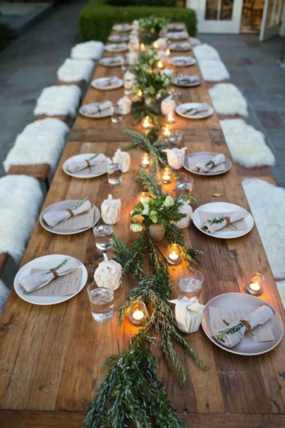 Rustic outdoor fall tablescape with long farm table, candlelight, and sheepskin over benches - Williams Sonoma. #falltablescape #farmhousefall #outdoorentertaining