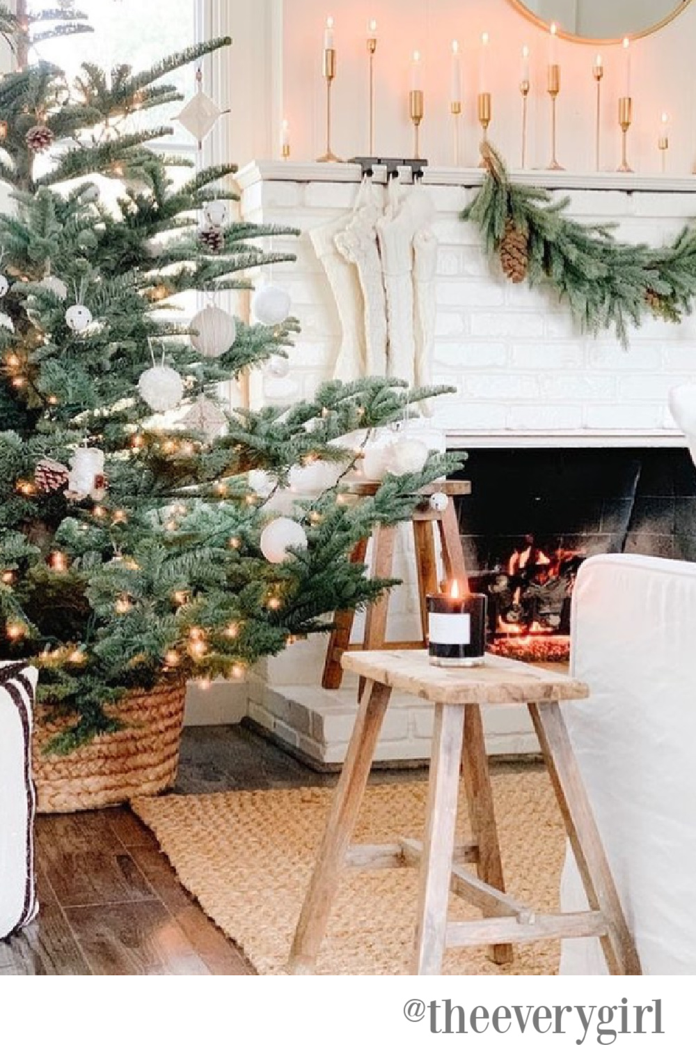Farmhouse Christmas decor in a living room with white brick fireplace - The Every Girl. #whitechristmas #farmhousechristmas #christmastrees