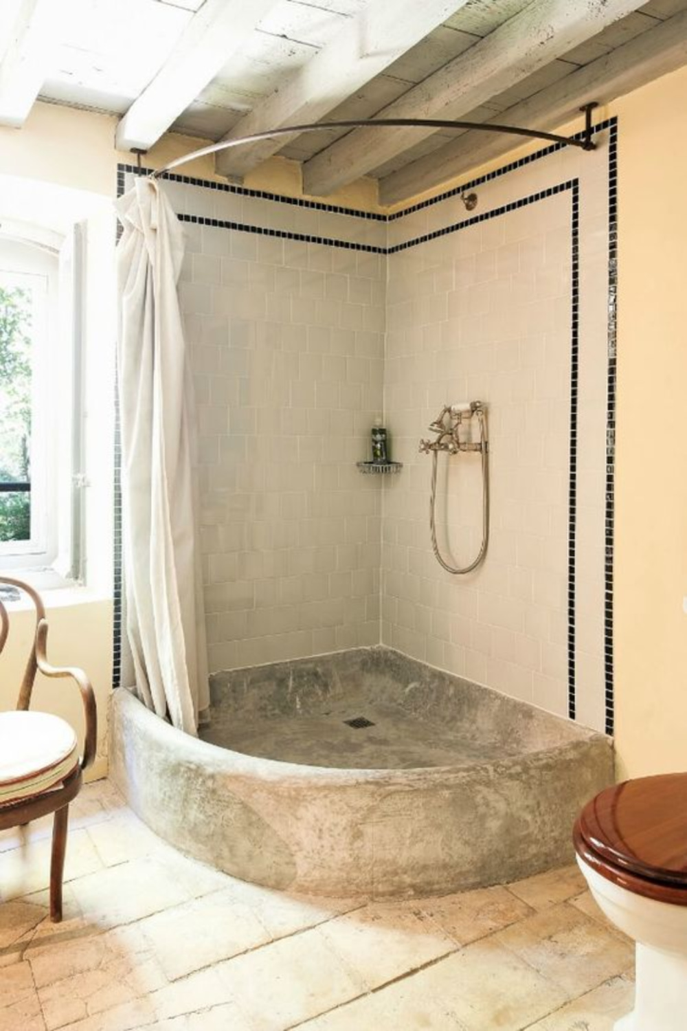 Old world style shower in a bathroom in a French chateau - Haven In. #stoneshower #bathroomdesign #oldworldstyle