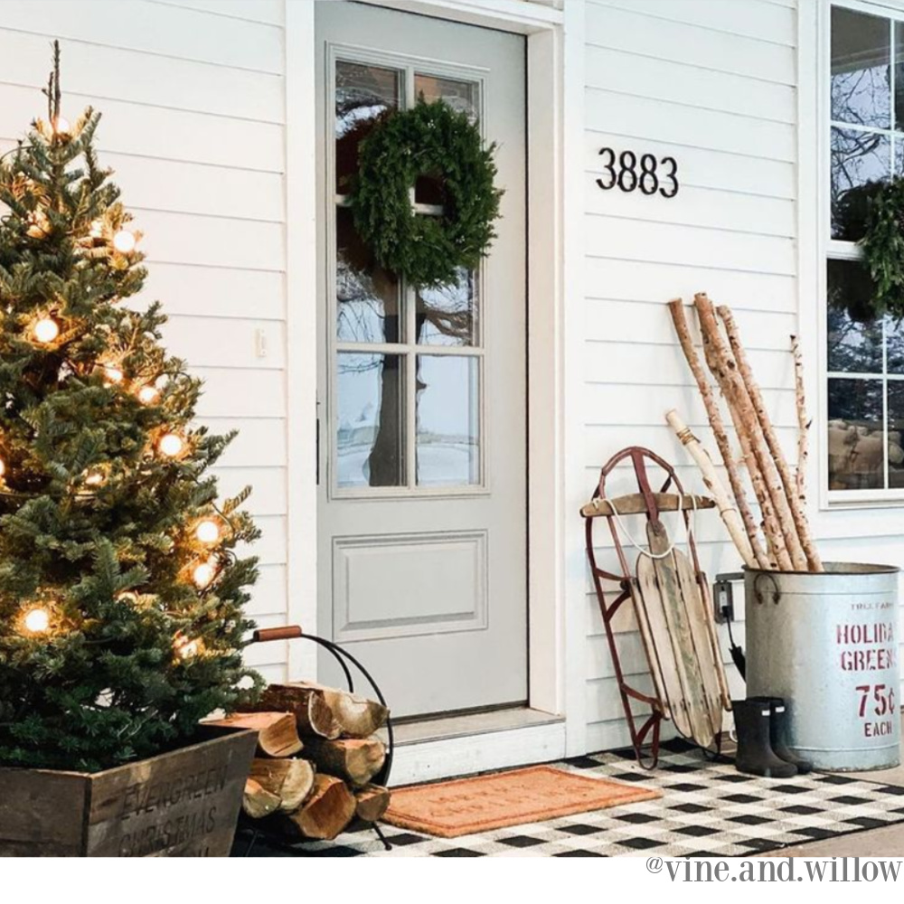 Beautiful Christmas decor on a country porch with tree and sled - Vine and Willow. #christmasdecor #farmhousechristmas