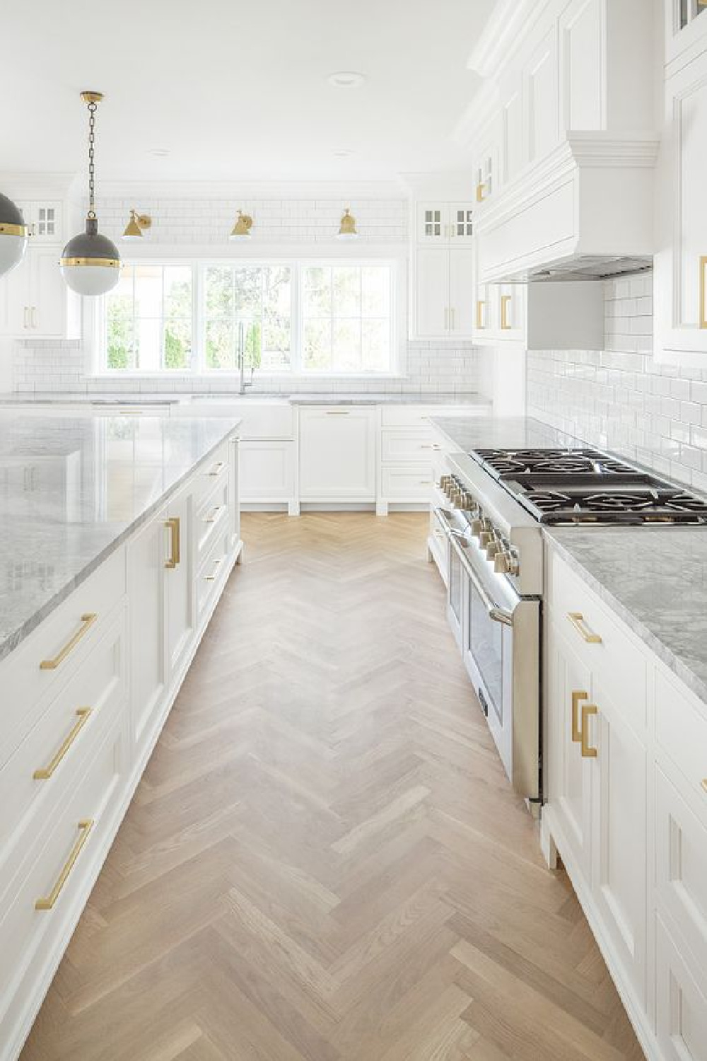 White kitchen with brass hardware, marble counters, herringbone hardwoods - design by the Fox Group. #whitekitchens #herringbonefloor #modernfarmhouse